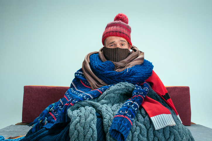 cold man bundled up on couch
