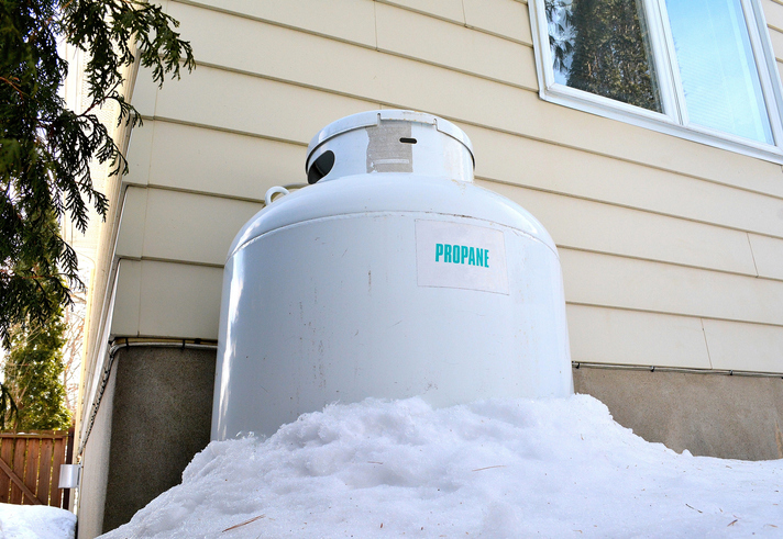 propane tank beside house in snow