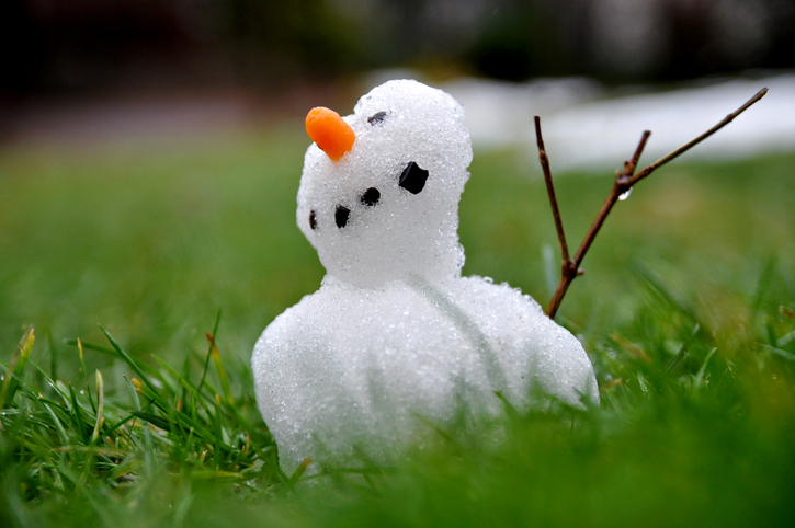 small snowman melting in spring