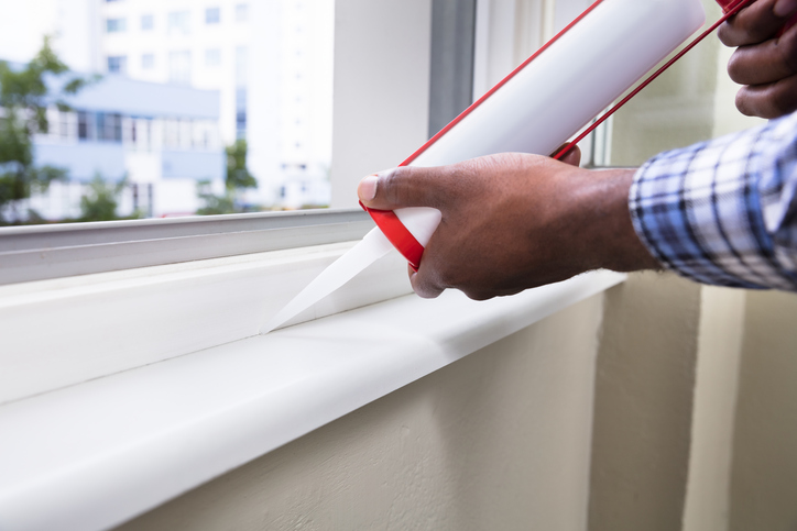 person caulking window