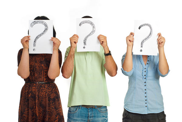 Three people holding question marks.